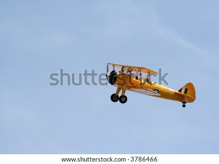 A bright yellow biplane gliding through the sky.