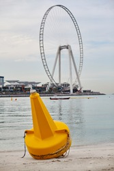 A bright yellow buoy lies on the shore against the background of the island Bluewater and wheels of the Eye Dubai
