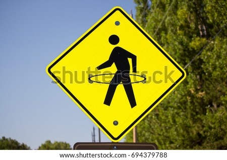 A bright yellow pedestrian crosswalk sign with a hula hoop drawn onto it.
