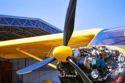 A bright yellow plane is on the engine maintenance service.
