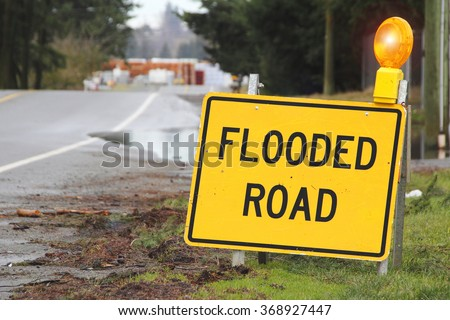 A bright yellow sign warns motorists that the road is flooded/Outdoor Sign Stating Flooded Road/A bright yellow sign warns motorists that the road is flooded.  Stock photo ©