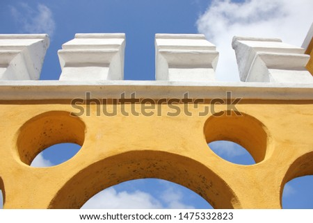 A brightly colored hand crafted architectural piece stands out against a bright blue sky filled with clouds in north east Portugal.