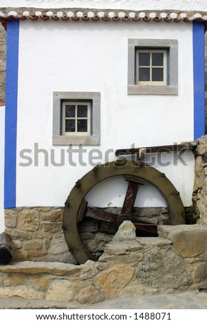 A brightly colored Portuguese facade with waterwheel