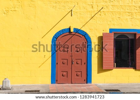 A brightly coloured image showing a doorway and window, with the shadows of a metal bracket from the bright sun. Taken in Bridgetown, Barbados. #1283941723