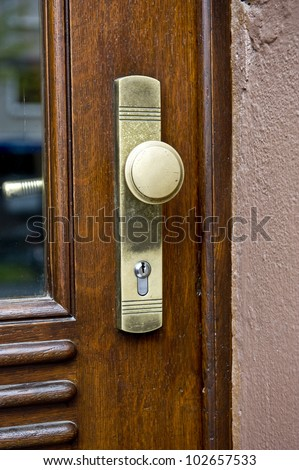 A brightly lit closeup of a golden door lock on a brown wooden door.