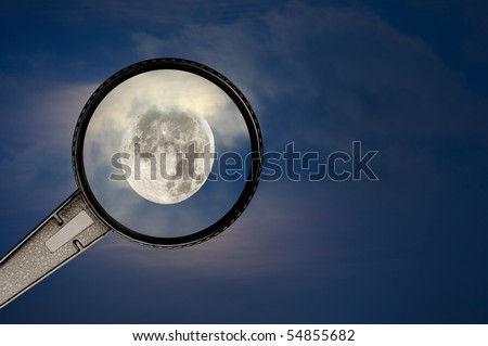 A brightly lit full moon lights up the cloudy, hazy sky while an onlooker uses a magnifying glass to view the moon.