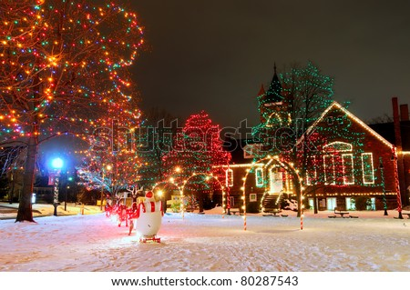 A brightly lit small-town Christmas display on the village square