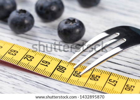 A brilliant dessert fork lies on a yellow centimeter near the mark of 60. Blueberries in the background. The concept of the berry diet for weight loss and body cleansing with parameters 36 24 36