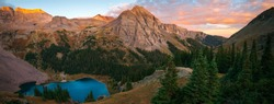A brilliant sunrise at the lower Blue Lake in Mount Sneffels Wilderness, Ridgeway, Colorado during the falls season. A backpacking adventure.