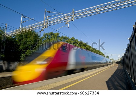 A British high speed passenger train passing through a station in the early morning.