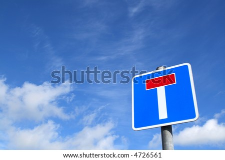 A British no through road T sign and a blue sky.