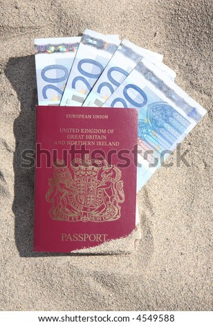 A British passport on a sandy beach with 20 Euro notes inside. - stock photo