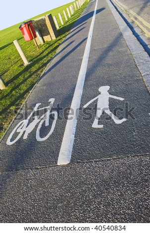 A British pavement, divided and signed for cyclists and pedestrians between an open field and a road.  Sunny day, blue sky.