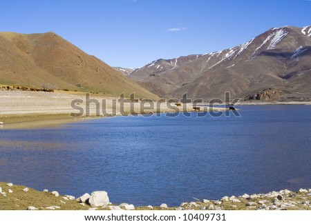 A broad blue river, its banks occupied by cattle sits beneath tall mountains with lingering patches of snow on them.