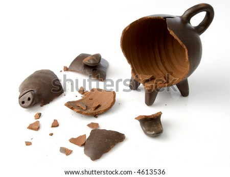 a broken and empty clay piggy money box over white background