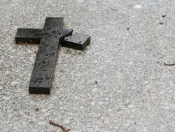 A broken black cross on the gray grave of a graveyard