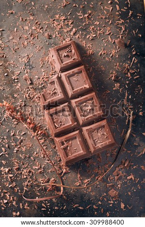 A  broken chocolate bar with some decorations, surraunded by flakes and a dried out twig, on a dark metal top.