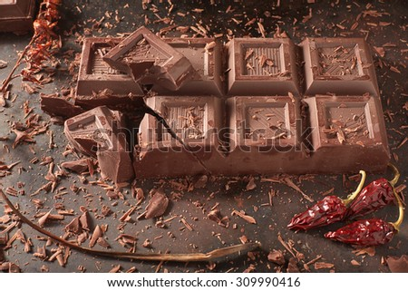A  broken chocolate bar with some decorations, surraunded by flakes, chili peppers and a dried out twig, on a dark metal top.