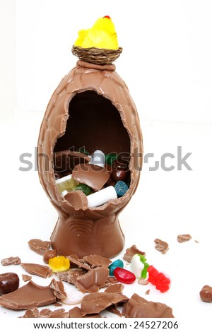 A broken chocolate easter egg isolate on white with hen on nest on top