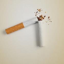 a broken cigarette on a beige background, symbolizing quitting smoking