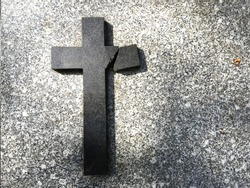 a broken cross on a grave of a cemetery