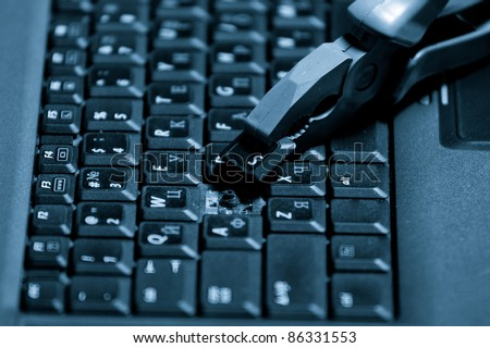 A broken laptop with a pliers. Closeup