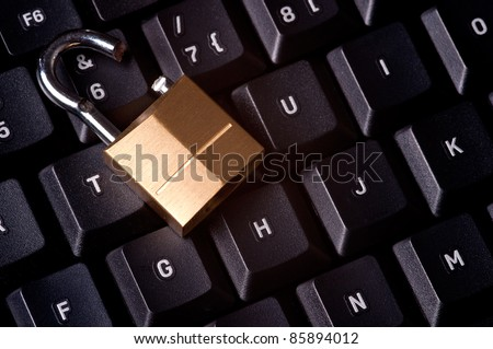 A broken padlock on top a computer keyboard to represent the concept of computer security breach