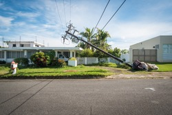 A broken telephone pole leans dangerously close to a house just outside of San Juan in Puerto Rico.