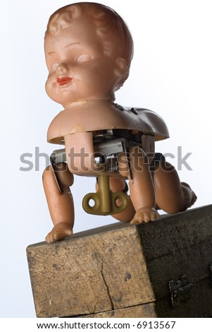 a broken windup crawling baby toy on a wood box