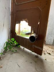 a broken wooden door with a big water pipe pierced through it. Weeds growing in the front corner of the room.