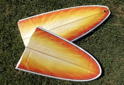 A Broken Yellow, Orange Surfboard On A Green Grass Field, Result Of Dangerous Surfing Conditions