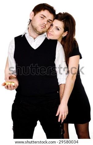 A brooding man with a wedding gift in a hand and a woman closely nestled to his back