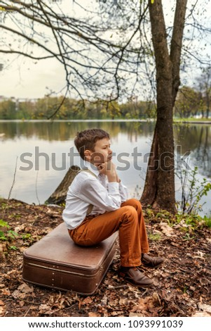 a brooding rustic simpleton fellow sitting on a retro old-fashioned suitcase on the bank of a river lake - Shutterstock ID 1093991039