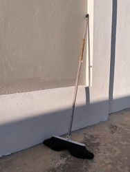 A broom leaning against the wall with direct sunlight and shadows. An old broom knows the dirty corners best.