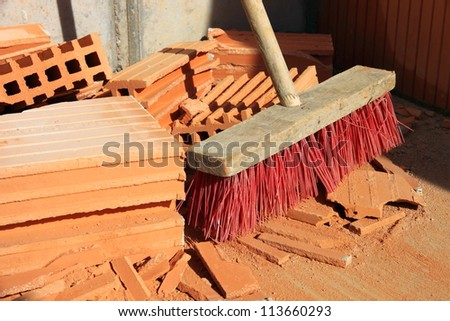 A broom with a pile of broken bricks on a construction site.