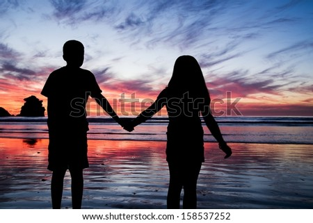 A brother and sister holding hands at sunset in Morro Bay, CA
