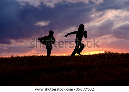 A brother and sister run and play at sunset.