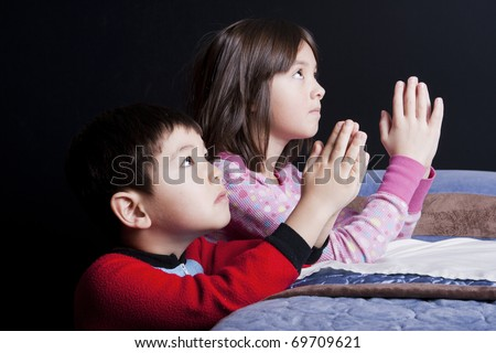 A brother and sister say their prayers just before bedtime.