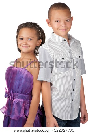 A brother and sister smile happily whilst standing close to each other.
