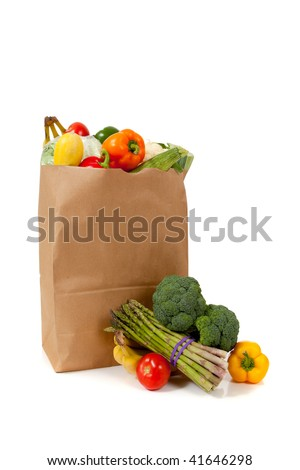 A brown grocery sack full of vegetables including broccoli, asparagus, peppers, tomatoes, celery, bananas on white background with copy space