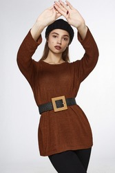 A brown-haired lady with raised hands is wearing black trousers, a brown knitted tunic dress and a black beret. The knitted dress is belted with a black raffia belt with a straw square buckle.