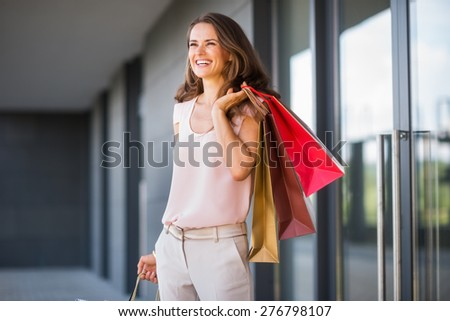 A brown-haired woman holding three shopping bags - gold, brown, and red - over her left shoulder laughs and smiles as she looks out into the distance. She is relaxed, and effortlessly stylish.