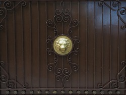 A brown iron fence with a wrought pattern and a golden lion head in the center. Full screen photo