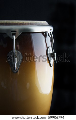 A brown Latin or African conga  drum isolated against a  black background in the vertical format with copy space.