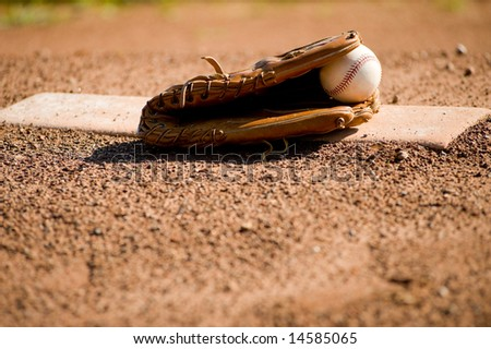 A brown leather baseball glove and a white leather baseball on a pitcher's mound at a baseball field, with copy space