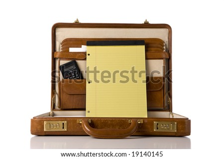 A brown leather briefcase with a blank legal tablet with copy space.  Includes calculator etc.