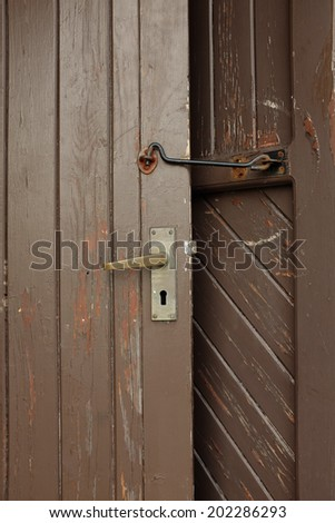 A brown painted door with a brass handle and lock held open by a metal hook.