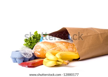 A brown paper bag full of groceries on a white background, with bread, milk, eggs, pasta, lettuce and bananas.  with copy space
