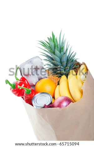 A brown paper bag stuffed with groceries.  Shot on white background. - stock photo