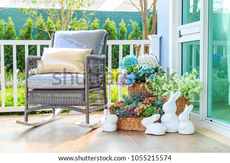 A brown pillow on wooden rocking chair and beautiful bouquet flower in the basket and white rabbit dolls on wooden floor in balcony with nature background. #1055215574